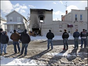 Firefighters from the Sandusky and Perkins Township fire departments view the apartment building in North Toledo. The firefighters place a Perkins Township Fire Department t-shirt and gloves on a board propped against the wall of the burned building.