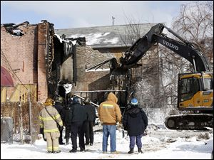 Investigators watch as fire debris is removed to allow for their investigation to continue.