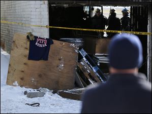 Firefighters from the Sandusky and Perkins Township fire departments view the apartment building in North Toledo.