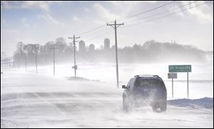 An SUV ventures past the St. Augusta, Minn., city limits sign on Stearns County Road 136 in near white-out conditions Sunday afternoon south of St. Cloud, Minn.