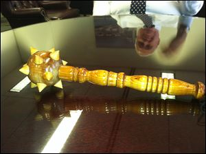 Chief of Staff Bob Reinbolt's image is reflected in a tabletop holding a spiked, wooden mace. Mr. Reinbolt first found it eight years ago when he was working for Mayor Carty Finkbeiner.