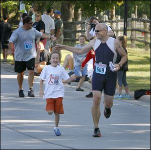 Joey Boyle, 8, left, joins his father, Joe Boyle, for the last 50 yards of Sylvania Triathlon/Duathlon in Sylvania in August. Mr. Boyle wants to cross the finish line before he starts a new round of chemotherapy treatments.