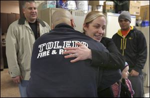 Jamie Armstrong hugs firefighter Jason Mercurio after she delivered food Saturday to Station 11. Behind her is her friend Kevin Nally and her son Shaun Wilson, 15.