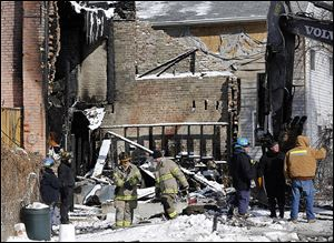 Investigators begin examining the remains of the apartment building on Magnolia Street in North Toledo where Pvts. Stephen Machcinski and James Dickman were killed battling a fire Sunday afternoon.