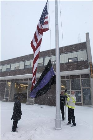 Deputy Toledo Fire Chief Brian Byrd, acting Deputy Chief Richard Syroka, and Battalion Chief John Kaminski lower the U.S. flag to half staff, and raise a funeral flag, at Toledo Fire and Rescue headquarters on North Huron Street,  early today in honor of firefighters Stephen A. Machcinski and James A. Dickman who were killed Sunday.
