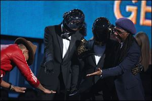 Pharrell Williams, left, presents the award to Thomas Bangalter, second from left, and Guy-Manuel de Homem-Christo of Daft Punk, and Nile Rodgers for best pop duo/group performance for 'Get Lucky.'