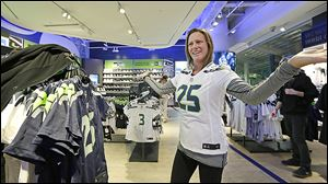 Ellen Kelly turns to a companion to help her decide as she tries on a Seattle Seahawks' jersey at the team store in Seattle. New York City officials hope  Super Bowl XLVIII fans like Ms. Kelly will bring a steady stream of business when they converge on New York City for the big game Feb. 2.