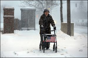 Harold Knapp of Toledo makes his way through the snow downtown, where many residents must walk to bus stops.