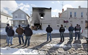Firefighters from the Sandusky and Perkins Township fire departments view the apartment building in North Toledo where firefighters Stephen Machcinski and James Dickman were killed. Private Dickman was a Perkins Township firefighter before joining the Toledo department.