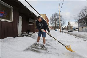 Tim Dzenis clears the snow outside his business, Tim & Ed's Bar & Grill, in his shorts, although the temperature is  about 10. Mr. Dzenis says he doesn't mind if it's 100 in the summer, and wonders whether he doesn't store all that heat to help him get through the winter.