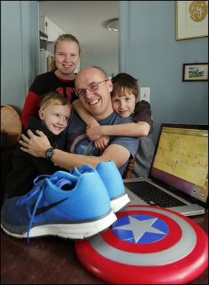 Joe Boyle is embraced by his children: Mark, 5, left, Ellie, 11, and Joey, 8. He is ready for his run; he has his new running shoes, his Captain America shield, and the run's route on his computer.