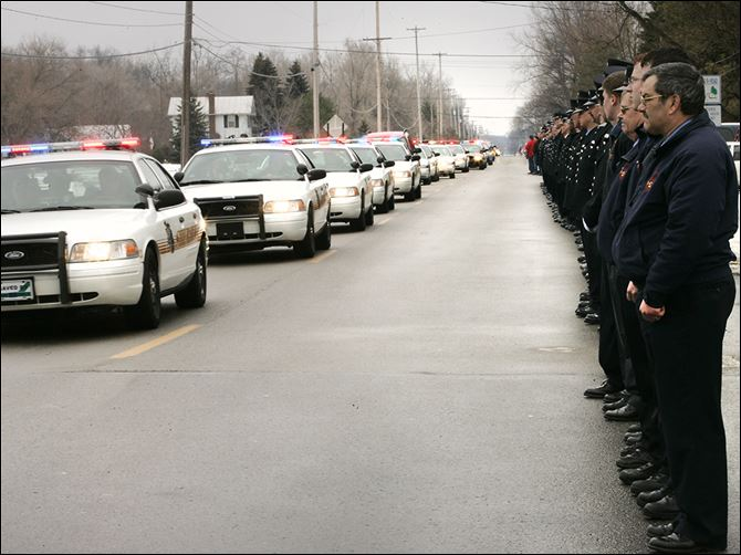 n3dressel Firefighters and police officers watch the procession to the cemetery during Toledo Detective Keith Dressel's funeral services.