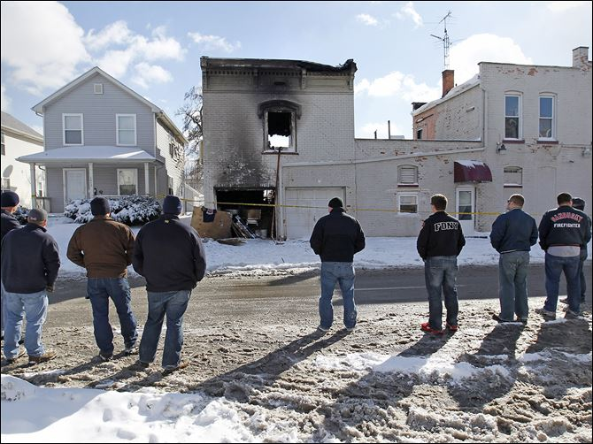 n3scene-2 Firefighters from the Sandusky and Perkins Township fire departments view the apartment building in North Toledo where firefighters Stephen Machcinski and James Dickman were killed. Private Dickman was a Perkins Township firefighter before joining the Toledo department.