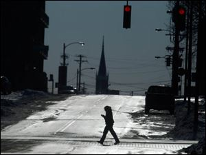 A pedestrian crosses Ontario Street while walking on Monroe Street, Tuesday, Jan. 28, 2014.
