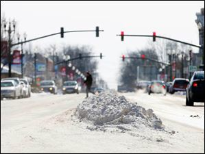 A long pile of snow separates the two sides of traffic on Main St. in Bowling Green.