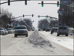 A long pile of snow separates the two sides of traffic on Main St. in Bowling Green on Tuesday, Jan. 28, 2014.