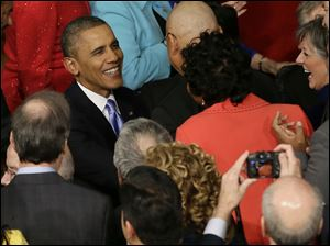 President Barack Obama is greeted as he arrives to give his State of the Union address on Capitol Hill.