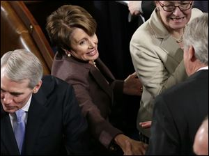 House Minority Leader Nancy Pelosi of Calif., center, and Sen. Rob Portman, R-Ohio, arrive for the State of the Union address.