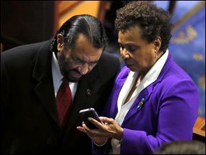 Rep. Sheila Jackson Lee, D-Texas shows Rep. Al Green, D-Texas, her mobile phone before President Barack Obama's State of the Union address.