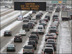 Traffic creeps along I-55 in north Jackson, Miss., today as ice and snow flurries cause difficult driving conditions.