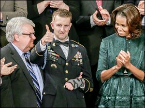Army Ranger Sgt. 1st Class Cory Remsburg acknowledges applause from First Lady Michelle Obama and others during the President's speech.