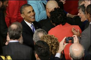 President Barack Obama is greeted as he arrives to give his State of the Union address on Capitol Hill in Washington.