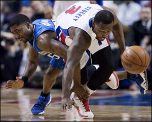 Orlando Magic guard E'Twaun Moore, left, trips up Detroit Pistons guard Rodney Stuckey (3) while chasing a loose ball during the first half.