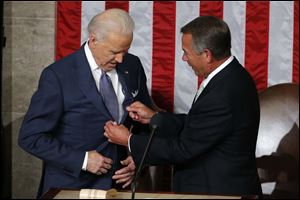 House Speaker John Boehner of Ohio adjusts Vice President Joe Biden's lapels.