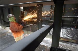 Larry Norman of Foundation Steel LLC, Swanton, removes a rusted handrail from the Craig Bridge.