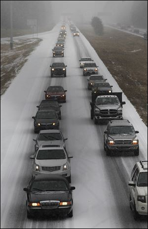 Vehicles moves slowly on Interstate 575 in North West Ga., Tuesday near Kennesaw, Ga. Georgians stocked up on ice-melting chemicals, school systems closed, and road crews prepared to clear snow and ice from highways as a winter storm took aim.
