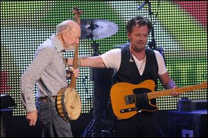 Pete Seeger is welcomed onstage by John Mellencamp during the Farm Aid 2013 concert at Saratoga Performing Arts Center in Saratoga Springs, N.Y. Seeger, an American troubadour, folk singer, and activist, died in New York on Monday at age 94. He had performed in Toledo at least three times.