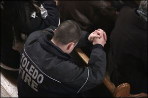 Station 21 Toledo firefighter Kyle Vasko prays during mass at the Historic Church of St. Patrick in Toledo.