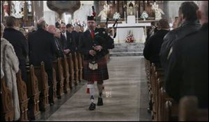 Chief Matt Hart plays Amazing Grace with his bagpipes during mass to honor the lives of Toledo firefighters Stephen A. Machcinski and James Dickman at the Historic Church of St. Patrick in Toledo.