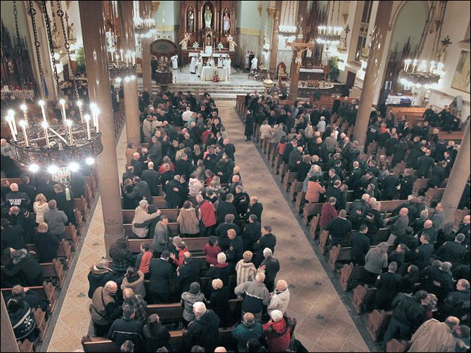 30n5mass-1 Nearly 1,000 local and retired firefighters and their families gather for Mass at the Historic Church of St. Patrick in honor of Toledo firefighters Stephen Machcinski and James Dickman, who died on duty Sunday.