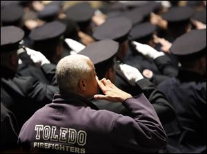 Toledo Firefighters salute during the Last Alarm funeral service.