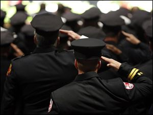 Firefighters salute during the Last Alarm funeral service.