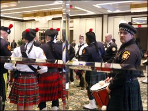 Roger Kerner, with The Toledo Firefighters Pipes and Drums, is reflected in the mirror at the Park Inn while waiting with other national members of the Pipes and Drum Corps.