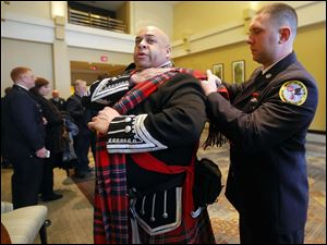 Lieutenant Mike Elston, with the Virginia Highlands Pipes and Drums, left, gets help putting on his uniform by Mike Sansone, Asst. Chief Engineer at New City Fire Department, right, with the The Rockland County Firefighters Pipes and Drums.