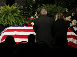 Toledo Mayor D. Michael Collins and his wife Sandra Drabik pause in front of  the casket of Stephen Machcinski.