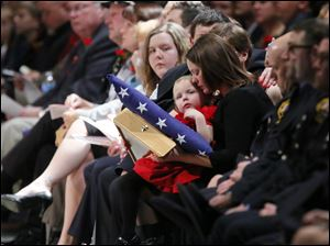 Paige Dickman, 3, daughter of Toledo firefighter James Dickman, holds an American and Ohio flags while sitting on the lap of her mother Jamie, wife of Mr. Dickman.
