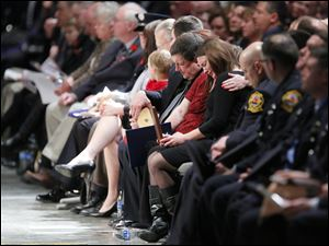 Jamie Dickman, wife of James Dickman, is consoled as she holds his IAFF Medal of Honor during the Last Alarm funeral service at SeaGate Convention Centre.