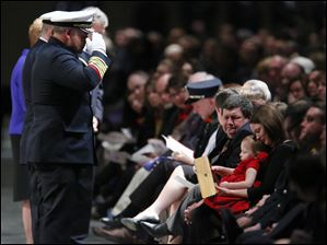 Paige Dickman, 3, daughter of Toledo firefighter James Dickman, holds an Ohio flag while sitting on the lap of her mother Jamie, wife of Mr. Dickman.