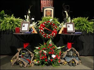 Tributes for firefighters James Dickman, left, and Stephen Machcinski stand beneath the stage.