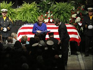 U.S Rep. Marcy Kaptur, left, and U.S. Sen. Sherrod Brown present the American flag to the family of Toledo firefighter Stephen A. Machinski.
