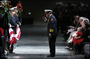 Toledo Fire Chief Luis Santiago salutes the casket of James Dickman as Private Dickman's wife, Jamie, right, holds their daughter Paige.