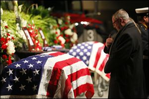 Mayor D. Michael Collins prays before the coffin of James Dickman, during the Last Alarm funeral service at SeaGate Convention Centre for Toledo firefighters Stephen Machcinski and James Dickman, Thursday, Jan. 30, 2014.