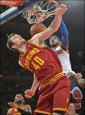 The Knicks' Carmelo Anthony dunks over the Cavaliers' Tyler Zeller during the first quarter Thursday night in New York. Anthony scored 18 in the first quarter alone.