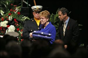 U.S. Rep. Marcy Kaptur and U.S. Sen. Sherrod Brown move forward to present American flags to the firefighters' families.