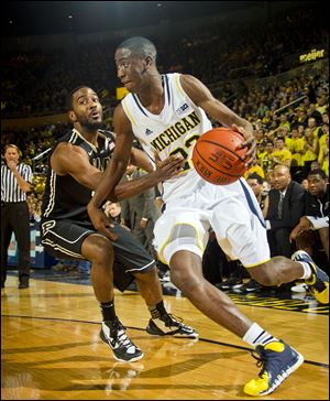 Purdue guard Rapheal Davis, left, defends Michigan guard Caris LeVert, who had 14 points and a career-high 11 rebounds for his first career double-double on Thursday night.
