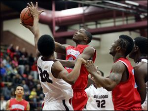 Bowsher's Dajuan King (13) goes to the basket against Scott's Chance Hawkins (20).